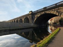 Oud verlaten spoorwegviaduct die het kanaal in de stadscentrum van Leeds kruisen dichtbij Whitehall-weg met overspannen nagedacht stock foto's