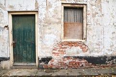 Oud veroordeeld huis met groene deur stock afbeelding
