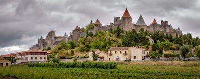 Oud versterkt de stadspanorama van Carcassonne met stormachtige hemel stock foto