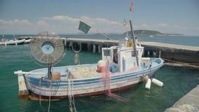 Oud vissersvaartuig met drijfnetten die dichtbij pijler en drijvend op golven, hobby worden geparkeerd stock video