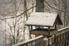 Oud vogelhuis op brench behandelde sneeuw in de winter Stock Foto