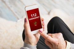 Oud vrouw het draaien alarmnummer 112 op telefoon Stock Foto's