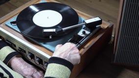 Oud vrouw het luisteren vinyl op speler stock video