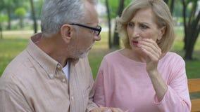 Oud wijfje die aan migraine, gevende echtgenoot ondersteunende vrouw, gezondheid lijden stock videobeelden