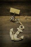 Oud wit anker met de houten klem van de pijlinktvisvorm en leeg stuk van document Stock Foto