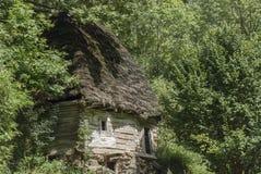 Oud zichzelf onderhoudend huis in het bos Stock Afbeeldingen
