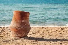 Oude aarden waterkruik die zich op het zand dichtbij het overzees bevinden stock afbeeldingen