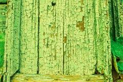 Oude abstracte grungeachtergrond met houten omheining met sporen van barst, krassen, schade, breuken, groen pellen stock foto's
