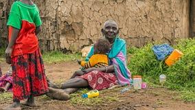 Oude Afrikaanse vrouw van Masai-stam die een baby in haar dorp houden Stock Fotografie