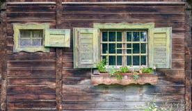 Oude alpiene hut - venster met bloemen Stock Fotografie