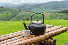 Oude aluminiumketel voor thee het koken en een glas thee Royalty-vrije Stock Afbeeldingen