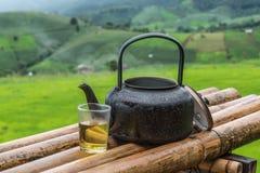 Oude aluminiumketel voor thee het koken en een glas thee Stock Foto's
