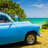 Oude Amerikaanse auto bij een strand in Cuba Stock Foto's