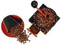 Oude antieke houten zwarte en rode koffiemolen, kop en gemorst royalty-vrije stock afbeeldingen