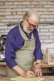 Oude artisanaal in glazen, overhemd en schort die een schets maken stock afbeelding