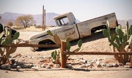 Oude Auto in het zandlandschap stock afbeeldingen