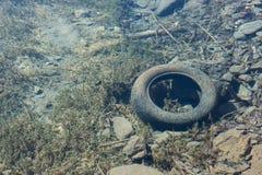 Oude autoband onder het duidelijke die water van een bergmeer wordt bekeken voor Royalty-vrije Stock Foto's