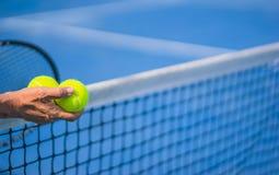 Oude Aziatische mensengreep twee tennisballen in rechtse, selectieve nadruk, vage racket, netto en blauwe tennisbaan als achtergr stock foto's