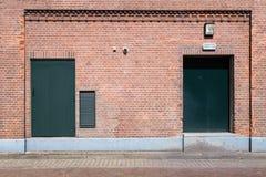 Oude bakstenen muur met groene deuren en straat Stock Fotografie