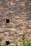 Oude bakstenen muur met ruw mortier en vierkante gaten dichtbij Hanoi Vietnam stock afbeelding