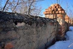 Oude bakstenen muur met torentjes die met instortingen begonnen Stock Fotografie