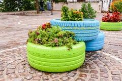 Oude banden die in geassorteerde kleuren voor een bloemplanter, moderne tuin geschilderd en gebruikt zijn royalty-vrije stock fotografie