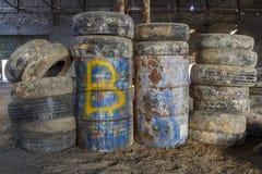Oude banden en vaten in een verlaten hangaar stock foto's
