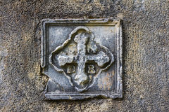 Oude bas-hulp in de vorm van een Christelijk kruis op de kerkmuur stock afbeeldingen