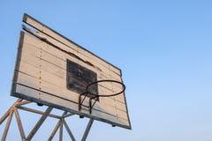 Oude basketbalrugplank, basketbalhoepels met blauwe hemelachtergrond stock foto