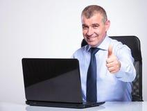 Oude bedrijfsmens die duimen van bureau tonen Stock Fotografie