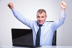 Oude bedrijfsmensentoejuichingen van achter laptop Royalty-vrije Stock Foto's