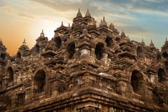 Oude beeldhouwwerken en standbeelden op de muren van de Borobudur-tempel tegen zonsopgang indonesië Java Island stock afbeelding