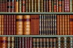 Oude bibliotheek van uitstekende harde dekkingsboeken op planken Stock Fotografie