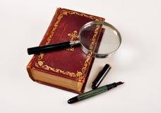 Oude Bijbel met meer magnifier en pen stock fotografie
