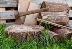 Oude bijl in de houten, gebarsten boomstomp op een achtergrond van gehakt brandhout Het voorbereidingen treffen voor koude de win Royalty-vrije Stock Afbeelding