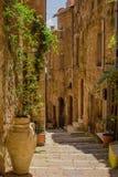 Oude binnenplaats in Pitigliano met vazen met bloemen op stai Stock Foto's