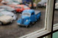 Oude blauwe auto van een venster Stock Afbeeldingen