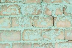 Oude blauwe bakstenen muur met schilverf stock afbeelding