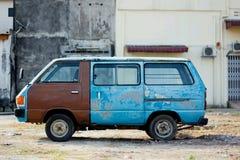 Oude blauwe bestelwagen bij de oude bouw Stock Afbeeldingen