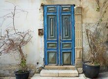 Oude blauwe deur tegen een oude steenmuur Stock Afbeeldingen