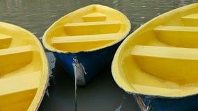 Oude blauwe en gele recreatieboot op meer Stock Foto