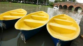 Oude blauwe en gele recreatieboot op meer Stock Afbeelding
