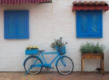 Oude blauwe fietsenrekken op de straat dichtbij de muur met vensters met houten blinden royalty-vrije stock afbeelding