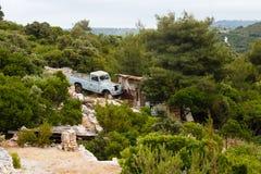 Oude blauwe Landroverbestelwagen die zich dichtbij plattelandshuisje in het bos in bergen op het eiland in Middellandse Zee bevin Stock Foto