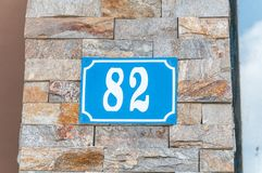 Oude blauwe uitstekende het metaalplaat nummer 82 van het huisadres op de decoratieve baksteenvoorgevel van woningbouw buitenmuur Royalty-vrije Stock Afbeelding