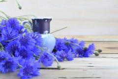 Oude blauwe waterkruik en blauwe korenbloemen Stock Afbeeldingen