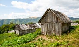Oude blokhuizen op weide in bergen royalty-vrije stock afbeeldingen
