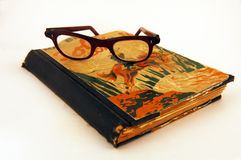 Oude boek en glazen stock foto