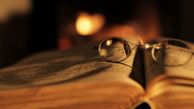 Oude boek en glazen voor de open haard stock video