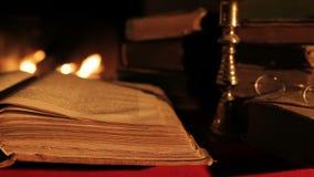 Oude boek en glazen voor de open haard stock videobeelden